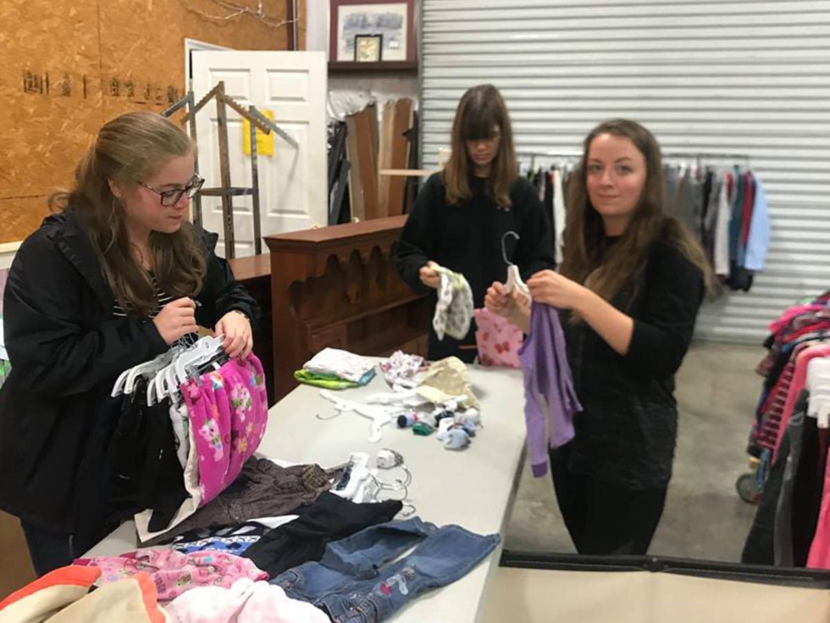girls sorting children's clothes